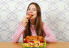 Den hungriga tonårs- flickan äter fega klumpar arkivfoto