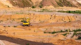 Den hydrauliska grävskopan fungerar på sandkalkstenvillebrådet, industriellt tungt maskineri royaltyfri fotografi