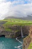 Den iconic vattenfallet av Gasadalur på Faroe Island och remoten Royaltyfria Foton