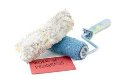 Den idérika bilden av den smutsiga och återanvände borsten för vit- och blåttrullmålarfärg med den vita fjädern förlade framme ar Arkivfoto