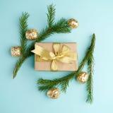 Den idérika Chistmas orienteringen gjorde av vintergrönska, den kraft gåvaasken med det guld- bandet och guld- garnering på blå b royaltyfri bild