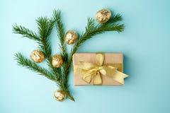 Den idérika Chistmas orienteringen gjorde av vintergrönska, den kraft gåvaasken med det guld- bandet och guld- garnering på blå b arkivbilder