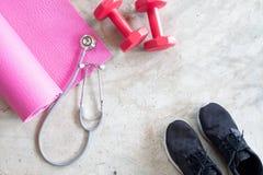 Den idérika lägenheten lägger av konditionutrustningar, stetoskopet och sportskor på konkret golv Sunt royaltyfria bilder