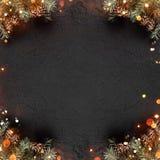 Den idérika orienteringsramen som göras av julgranfilialer med, sörjer kottar på mörk feriebakgrund med ljus arkivfoton