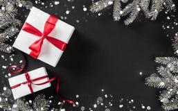Den idérika orienteringsramen som göras av julgranfilialer, sörjer kottar, gåvor med det röda bandet på mörk bakgrund royaltyfri fotografi