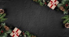 Den idérika orienteringsramen som göras av julgranfilialer, sörjer kottar, gåvor på mörk bakgrund Tema för Xmas och för nytt år,  arkivfoton