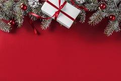 Den idérika orienteringsramen som göras av julgranfilialer, sörjer kottar, gåvor, röd garnering på röd bakgrund royaltyfri fotografi