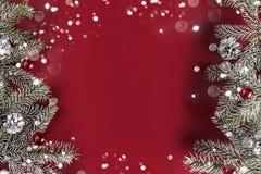 Den idérika orienteringsramen som göras av julgranfilialer, sörjer kottar, gåvor, röd garnering på röd bakgrund royaltyfria foton