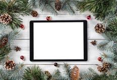 Den idérika orienteringsramen som göras av julgranfilialer, sörjer kottar och minnestavlaPC på vit träbakgrund Xmas och nytt år royaltyfri foto