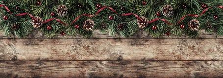 Den idérika orienteringsramen som göras av julgranfilialer, sörjer kottar och röd garnering på träbakgrund Tema för Xmas och för  arkivbilder