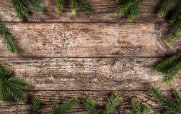 Den idérika orienteringsramen som göras av julgranfilialer, sörjer kottar på träbakgrund arkivfoton