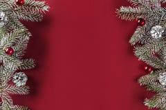 Den idérika orienteringsramen som göras av julgranfilialer, sörjer kottar, röd garnering på röd pappers- bakgrund arkivbilder