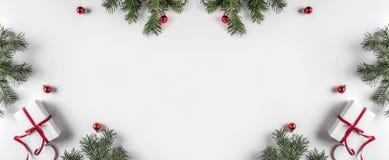 Den idérika ramen som göras av julgranfilialer på vitbokbakgrund med röd garnering, sörjer kottar arkivbild