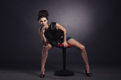 Den idérika sexiga flickan i en svart väst sitter Royaltyfri Fotografi