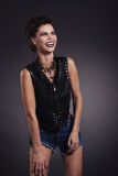 Den idérika sexiga flickan i en svart väst skrattar Royaltyfri Fotografi