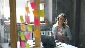 Den idérika unga affärskvinnan lyssnar till musik i hörlurar som dansar, medan arbeta på skrivbordet med bärbara datorn i modernt lager videofilmer