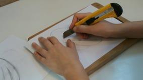 Den idérika unga kvinnan klippte stencilen genom att använda ett träbräde arkivfilmer
