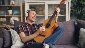 Den idérika unga mannen spelar gitarren och sjunger favorit- sång som lyssnar till musik i hörlurar som kopplar av i modernt stock video