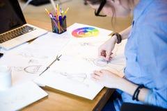 Den idérika kvinnamodeformgivaren i exponeringsglas som sitter och drar, skissar Royaltyfri Foto