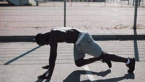 Den idrotts- afrikansk amerikanmannen böjer snabbt den främsta plankan för ben i gatan nära sportstadion Kondition hälsa arkivfilmer