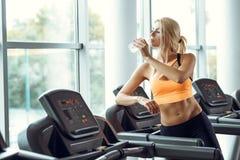 Den idrotts- blonda kvinnan är dricksvatten på trampkvarnen i idrottshall Royaltyfri Fotografi