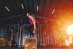 Den idrotts- flickan boxas hoppövningar på idrottshallen Arkivbild
