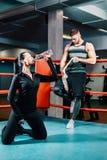 Den idrotts- flickan dricker rent vatten från en flaska i en boxningsring en idrotts- muskulös man står bakom fotografering för bildbyråer