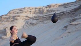 Den idrotts- flickan i en svart överkant, övning sparkar, sparkar fot framme av ballongen, fyllt med kulört vatten Flickasparkar stock video
