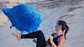 Den idrotts- flickan i en svart överkant, övningssparkar, sparkar fot framme av ballongen Flickasparkar sväller med hennes fot, o lager videofilmer
