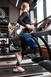 Den idrotts- flickan med iklätt långt blont hår en sportswear kör på trampkvarnen framme av fönstren in royaltyfri fotografi