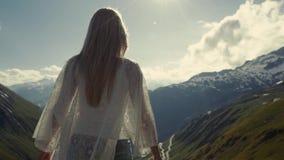 Den idrotts- flickan står på överkanten av fjällängbergen Hon lyfter hennes händer till solen stock video