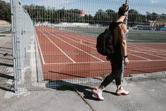 Den idrotts- grabben i iklädd svart sportkläder för huvudbindel med ryggsäcken på hans skuldror promenerar lekplatsstaketet royaltyfri foto
