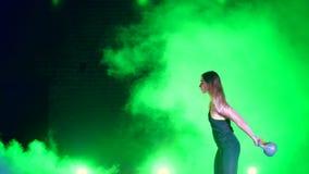 Den idrotts-, härliga unga kvinnan som gör olik styrka, övar med vikter På natten i ljuset av mångfärgat arkivfilmer