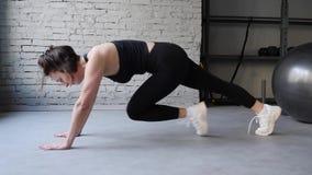 Den idrotts- h?rliga kvinnan g?r den rinnande plankan som delen av hennes arga kondition, rutin f?r bodybuildingidrottshallutbild arkivfilmer