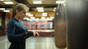 Den idrotts- kickboxing kvinnan kontrollerar hennes spikar och börjar att slå en stansa påse stock video