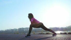 Den idrotts- kvinnan går in för sportar på flodbanken på soluppgång l?ngsam r?relse stock video