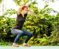 Den idrotts- kvinnan med dreadlocks gör squats i en parkera royaltyfri foto