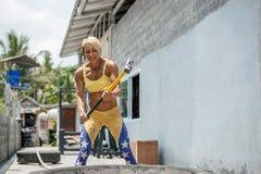 Den idrotts- kvinnan slogg ett gummihjul vid hammaren Crossfit royaltyfri foto