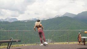 Den idrotts- kvinnan som gör kluven satt övning för enkelt ben med, parkerar höga byggnader för utrustning utomhus i bakgrund arkivfilmer