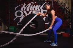 Den idrotts- kvinnan som gör någon crossfit, övar med ett tungt rep royaltyfria foton