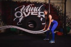 Den idrotts- kvinnan som gör någon crossfit, övar med ett tungt rep arkivbild