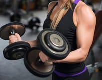 Den idrotts- kvinnan som pumpar upp, tränga sig in med hantlar Fotografering för Bildbyråer
