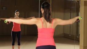 Den idrotts- kvinnan som pumpar upp, tränga sig in med hantlar Konditionmodell som ser i spegeln lager videofilmer