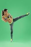 Den idrotts- kvinnan som utbildar hennes högt, sparkar in studion på grön backgro royaltyfri bild