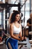 Den idrotts- lockiga flickan har en TRX-genomk?rare i den moderna idrottshallen mycket av solljus royaltyfria bilder