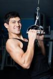 Den idrotts- manen fungerar ut på konditionidrottshallutbildning Arkivbild