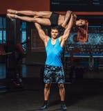 Den idrotts- mannen lyfter konditionflickan som vikt över himsself i idrottshall Arkivfoto