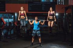 Den idrotts- mannen lyfter skivstången med två flickor som vikt och flickor som hänger från skivstång skivstång med två flickor p Arkivfoton