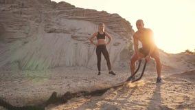 Den idrotts- mannen på övning runt om sandkullarna på solnedgången slår repet på jordningen och lyftte dammet arkivfilmer