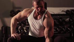 Den idrotts- mannen pumpar muskler i idrottshall stock video
